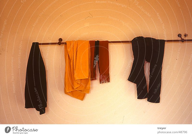 Clothes on clothes rail Hallstand Clothing Wall (building) Pants Scarf Shirt Towel Rod Yellow Red Brown Black White Orange