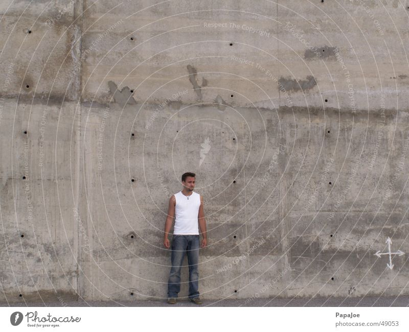 Human being Man White Wall (building) Stone Wall (barrier) Small Concrete Large Jeans Arrow Hollow