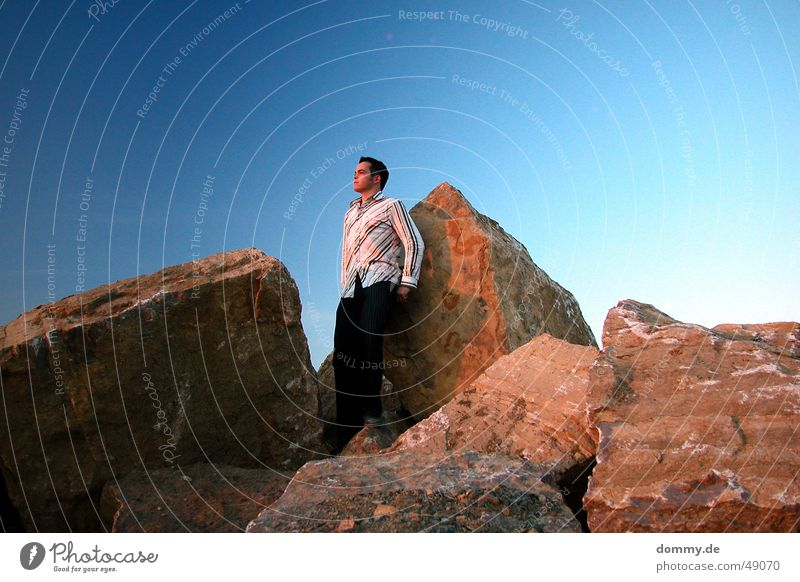 Sky Man Blue Sun Summer Far-off places Eyes Hair and hairstyles Stone Mouth Horizon Nose Rock Pants Shirt Lean