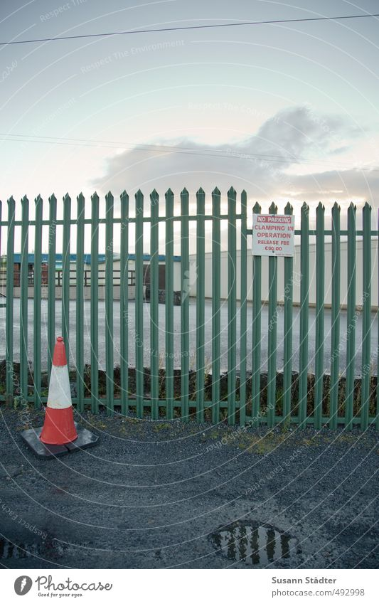 A o Industrial plant Street Lanes & trails Gloomy Town Divide Fence Fence post Traffic cone Road sign Puddle Pylon Colour photo Exterior shot Deserted Dawn