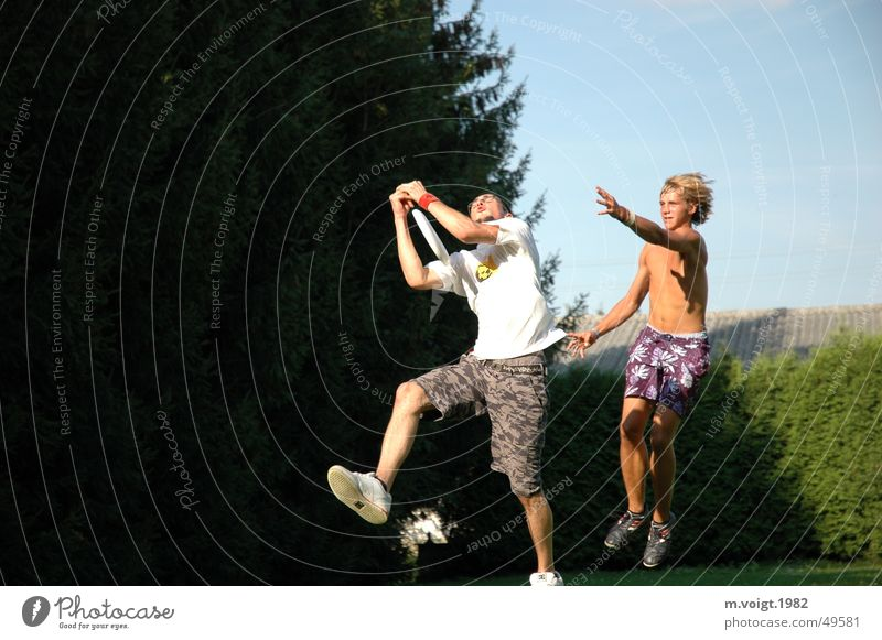 Ultimate Frisbee Colour photo Exterior shot Copy Space left Life Leisure and hobbies Young man Youth (Young adults) Man Adults 2 Human being Movement Fight Jump
