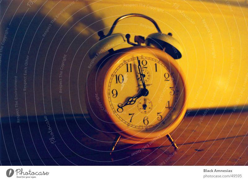 Alarm clock on the floor in front of the door casting a shadow Just before eight Clock face Yellow Flea market Loud Boredom Door Floor covering Shadow Time