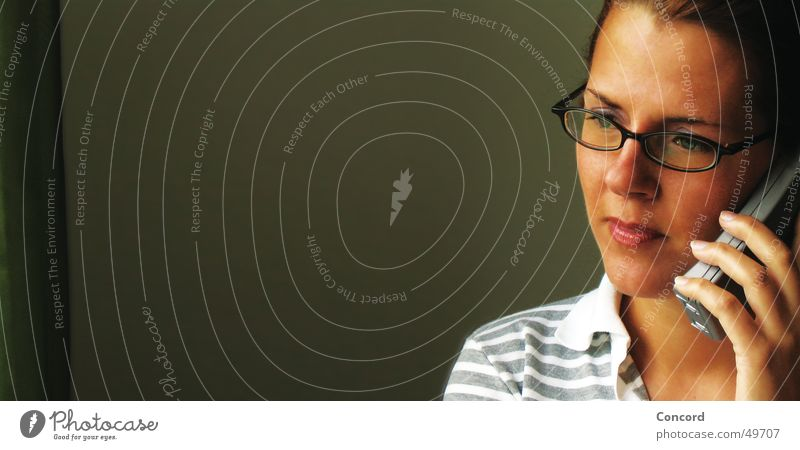 how's it going Woman Brunette Eyeglasses Cellphone Side Silhouette To talk Edge Watchfulness Concentrate Think Interior shot Portrait photograph Dark background