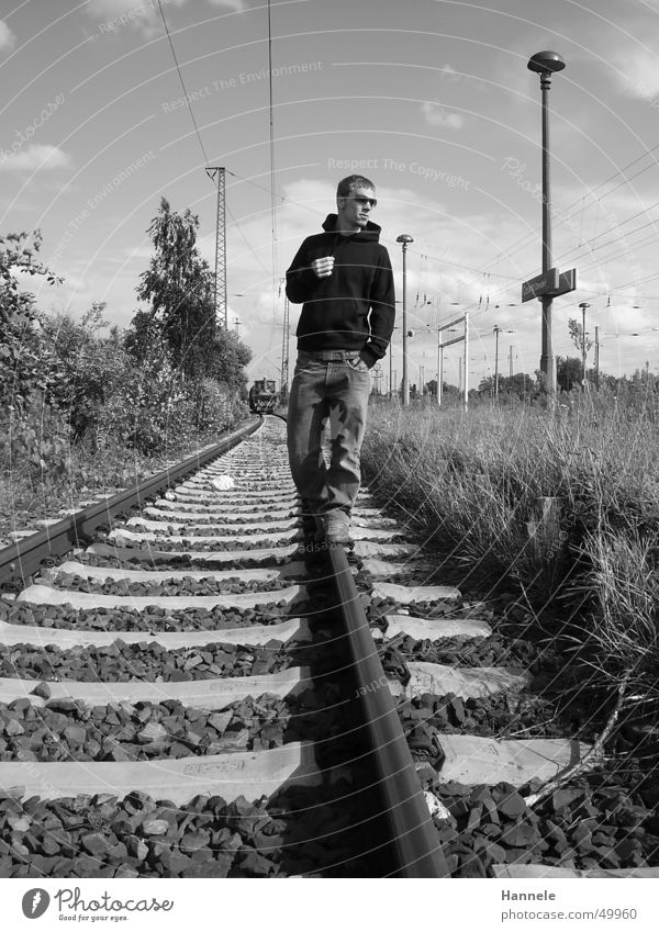 railway walker Railroad Man Masculine Railroad tracks Exterior shot Sunglasses Black White Meadow Posture Sweater Train station Cool (slang) Sky Jeans