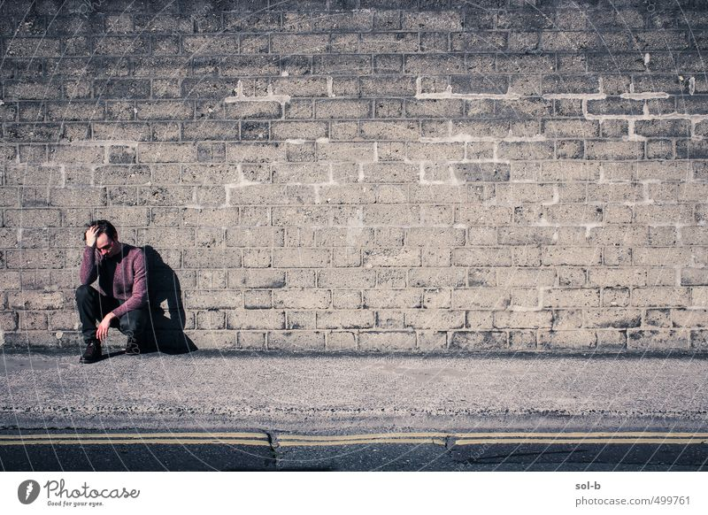 against a wall Unemployment Masculine Young man Youth (Young adults) 1 Human being 18 - 30 years Adults Town Downtown Wall (barrier) Wall (building) Street