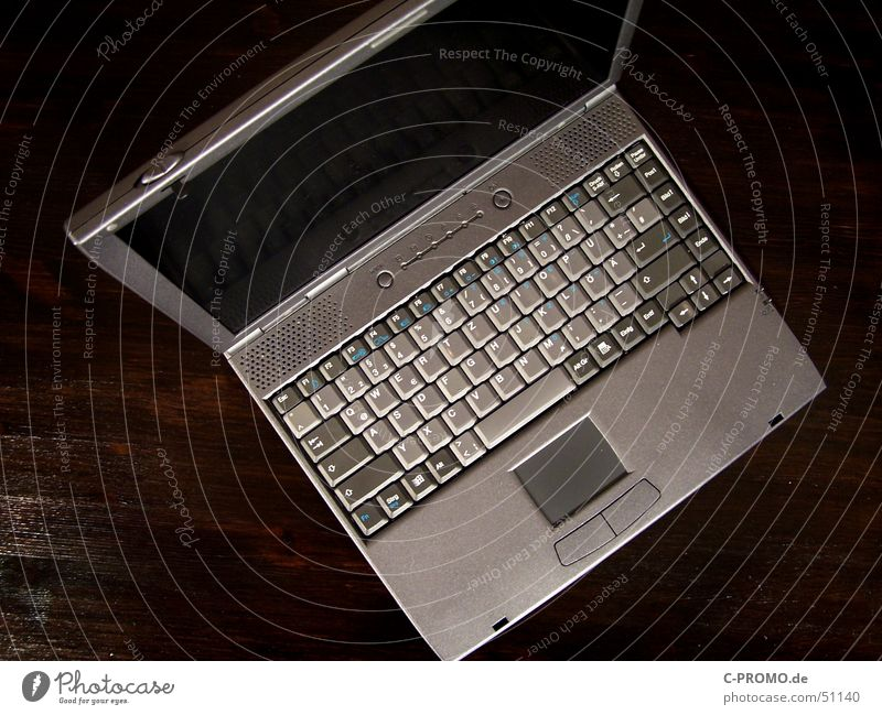 Grey laptop Touchpad Screen Flat Mobility Gray Brown Table Bird's-eye view Expensive Interior shot Electrical equipment Technology Media Keyboard Business