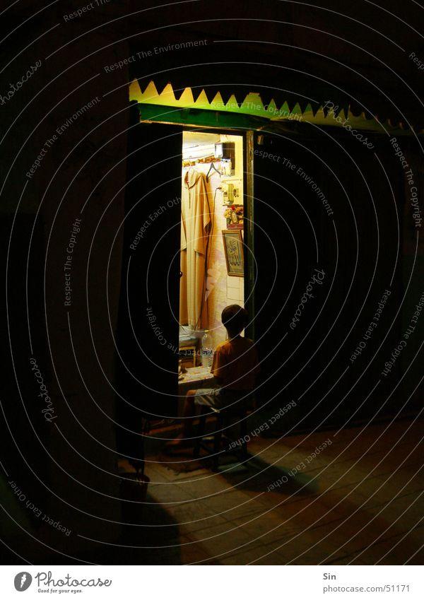 Hairdresser in Morocco Night Dark Light Shadow Door sitting in front of the door