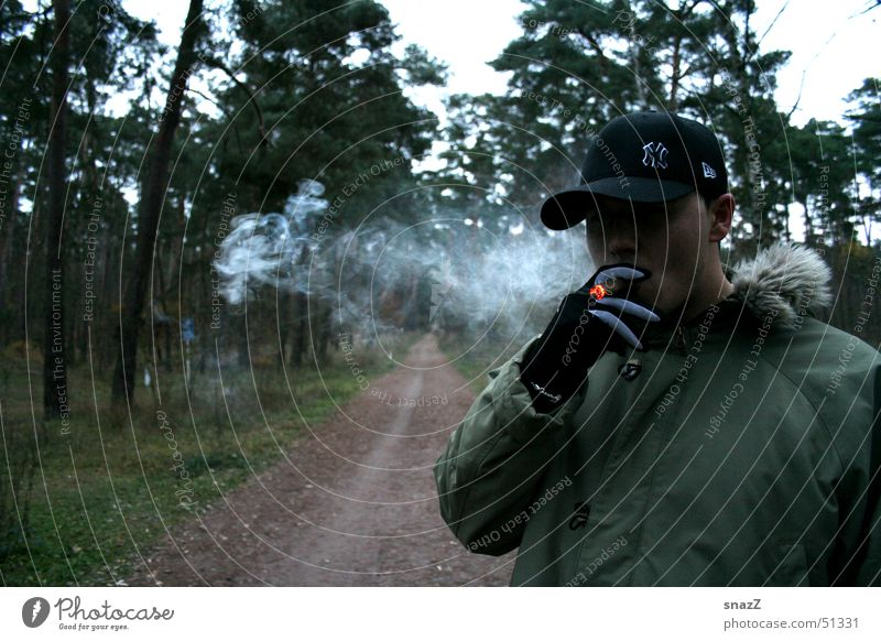 A short break on the way to happiness Cigar Cigarette Baseball cap Green Beige Forest Tree Black Gloves Exterior shot Smoking Grass Dark green Embers Recitative