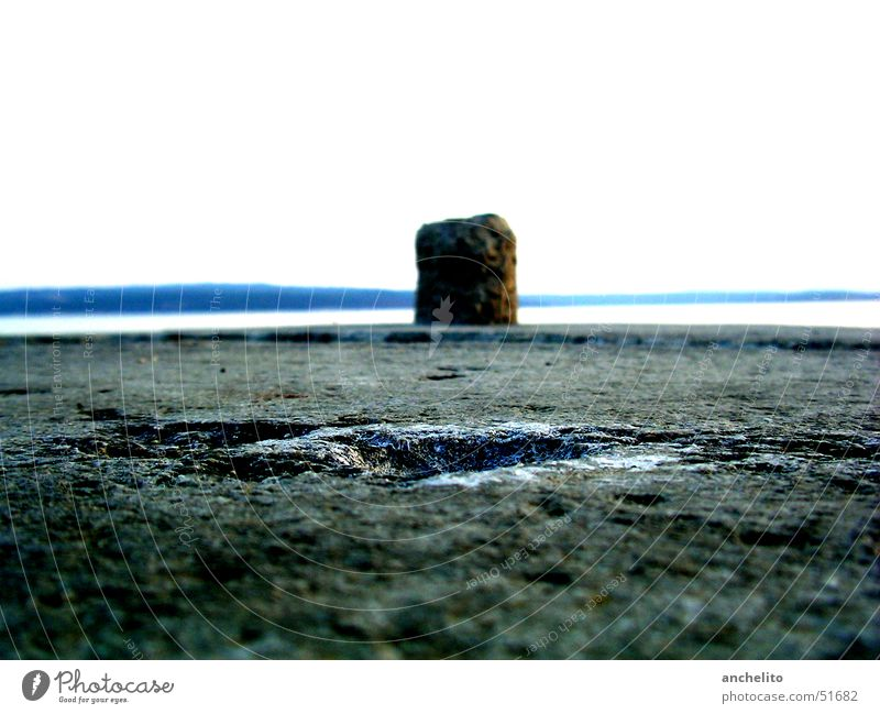 lonely bollard in front of the wide sea Bollard Asphalt Ocean Lake Gray Sky White Loneliness Far-off places Fastening Beach Coast pollard Stone Floor covering