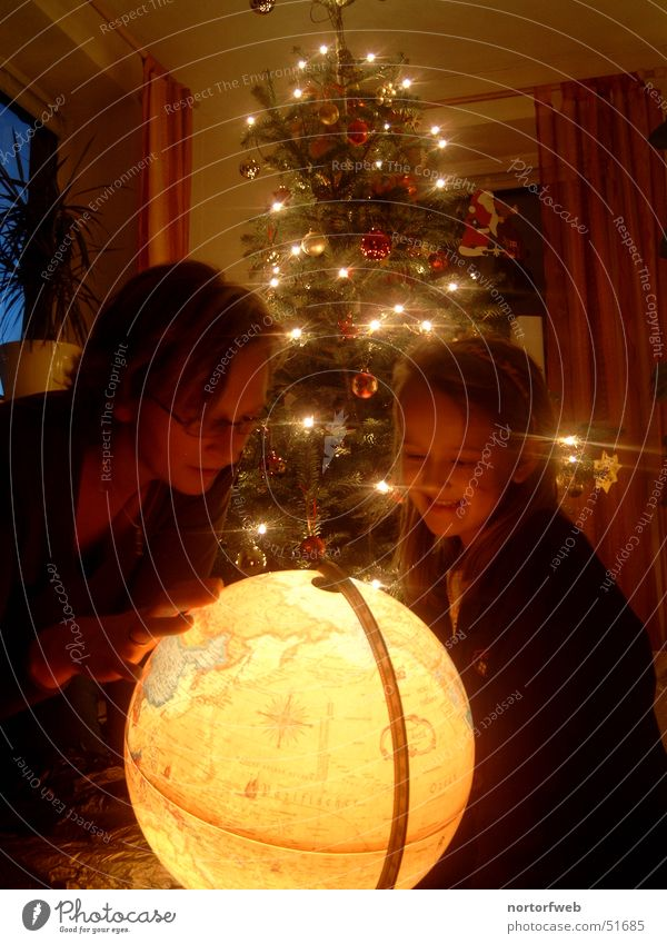 Child Family & Relations Christmas & Advent Joy Parents Light Moody Feasts & Celebrations Earth Gift Mother Fir tree Globe Interpretation Warm light