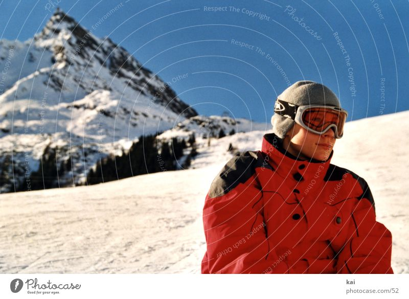 Human being Winter Mountain Snow Boy (child) Sports Orange Beautiful weather Peak Skiing Cloudless sky Jacket Slope Skier Winter sports Child