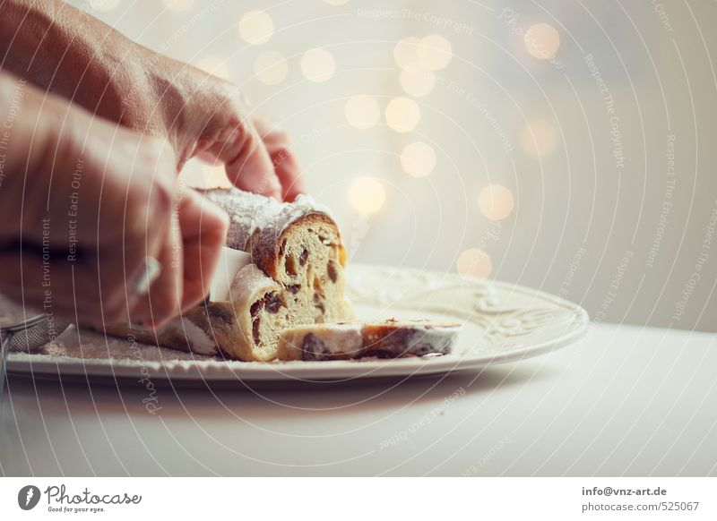 tunnel Food Dough Baked goods Cake Dessert Stollen Gold Christmas & Advent Knives cut Raisins Hand To hold on Colour photo Interior shot Studio shot