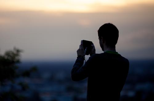 Man takes photo with his smartphone of the sunset over Freiburg Lifestyle Style Joy Leisure and hobbies Vacation & Travel Tourism Trip Sightseeing City trip