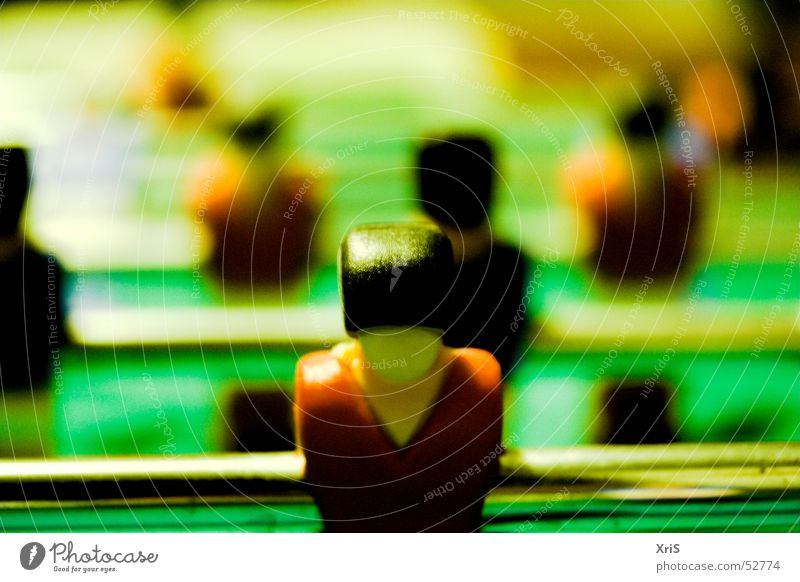 In the first row Table soccer Attacker Sports team Piece Shallow depth of field Colour photo Rod Green Row Behind one another Rear view Glittering