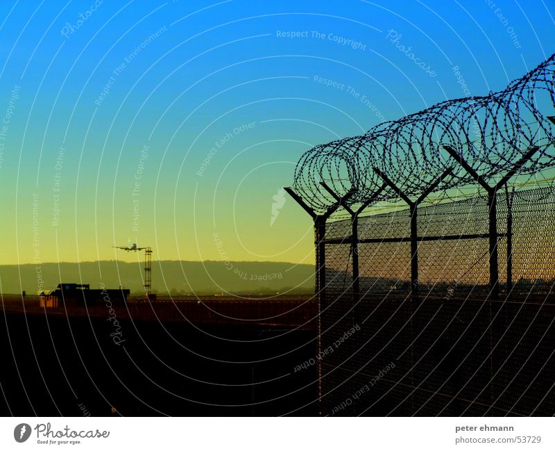 twilight flight Vacation & Travel Twilight Fence Yellow Arrival Barbed wire Hill Moody Light Dim Sunset Flying Blue Airplane landing Airport To put on Aviation