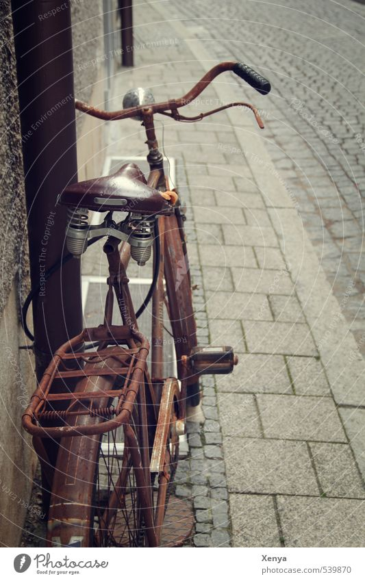 Wheel rust Bicycle Metal Old Retro Town Brown Romance Modest Refrain Rust Cobblestones Memory Nostalgia Ajar Break Bicycle saddle Subdued colour Exterior shot