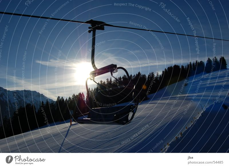 Backlit armchair Armchair Chair lift Driving Checkmark Winter Sunrise Forest Cold Artificial snow Back-light Gstaad Saanenland Seating Rope Sit Snow Sky