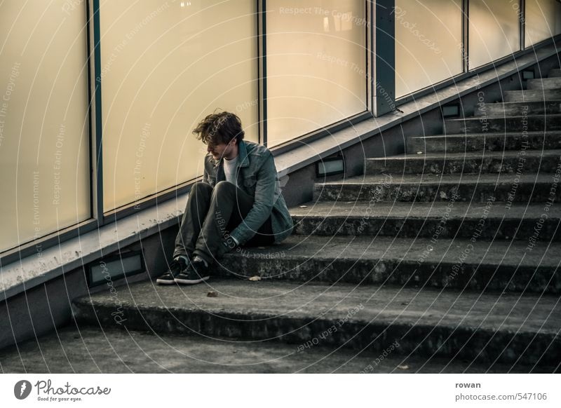 waiting Human being Masculine Young man Youth (Young adults) Man Adults Town Facade Window Dark Stairs Glas facade Diagonal Cold Sit Loneliness Wait Concern