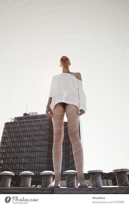 young, tall woman with very short hair stands on a chimney in front of a high-rise building Young woman Youth (Young adults) 18 - 30 years Adults Roof Chimney