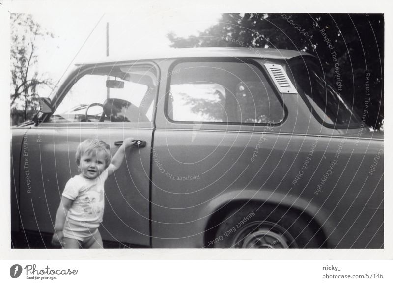 Let's get going. Girl Child Door handle Wheel rim Tree Black White Appealing Sun Sweet Trabbi East Car Sky Laughter