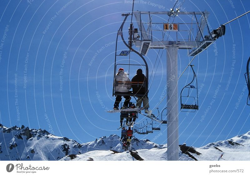 Winter Mountain Snow Sports In pairs Tall Beautiful weather Alps Snowcapped peak Upward Snowscape Blue sky Skier Snowboard Winter vacation Suspended