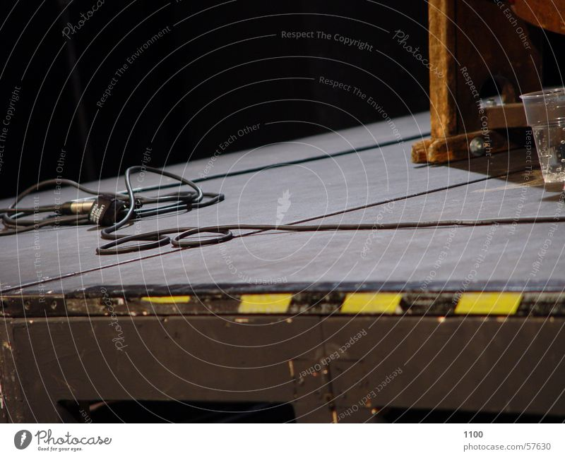 stage floor Stage Stage lighting Stripe Yellow Black Corner Microphone Floor covering Cable Glass Mineral water Respect Warning label Landing Wooden board
