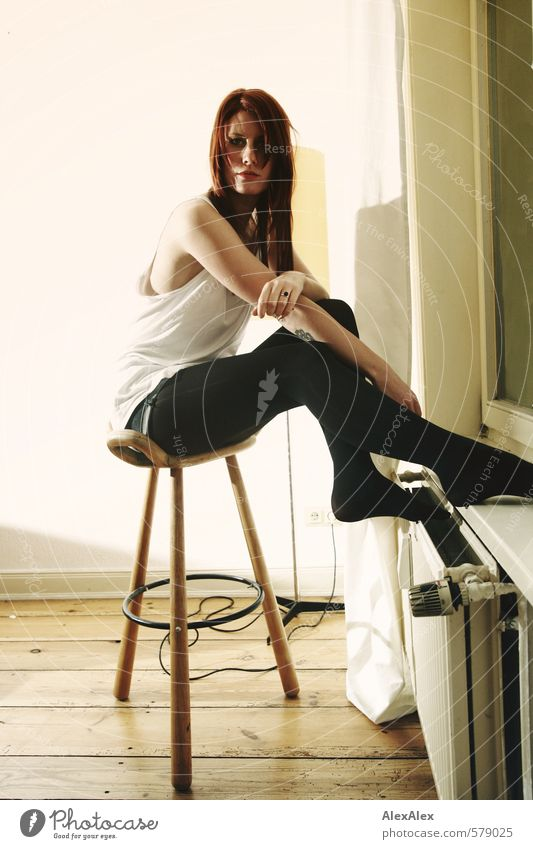 Young woman sitting on a stool by the radiator Youth (Young adults) Arm Legs 18 - 30 years Adults Shirt Tights Red-haired Long-haired Floorboards Heating Window