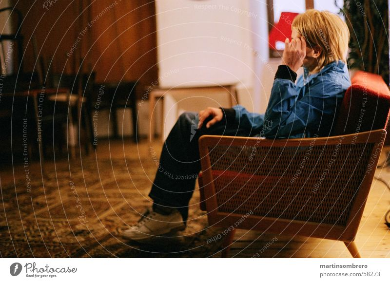 Thinking in the sofa Cozy Carpet Sofa Red Young woman Pants Sneakers Blonde Cool-headed Interior shot not light not dark Old wooden backrest blue jacket Sit