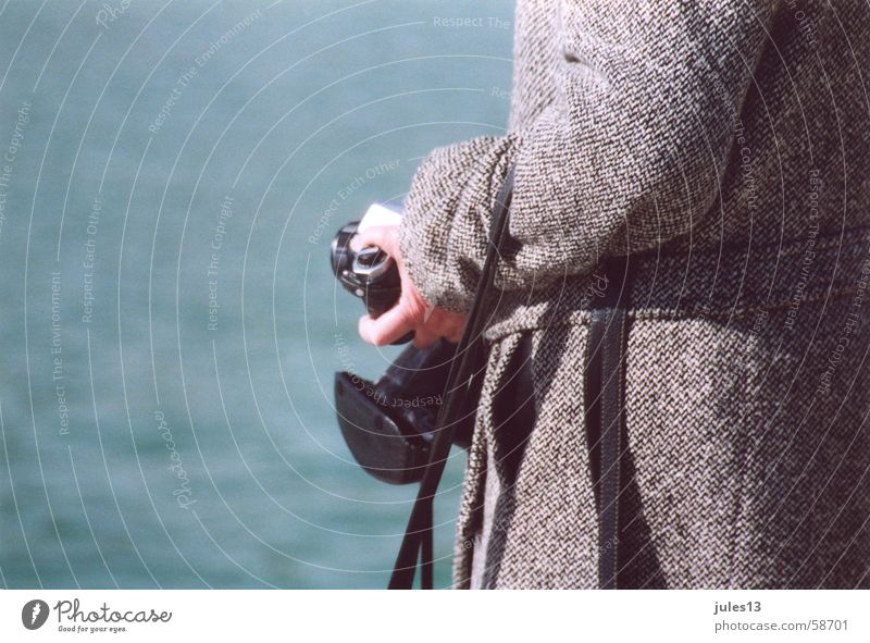out of hand Coat Gray Ocean Lake Exterior shot Hand Lady Blue Camera Detail Day Light Partially visible