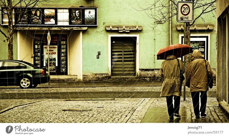 Cinema day. Umbrella Town Bad weather Human being Rain Street Cobblestones Sidewalk Jena