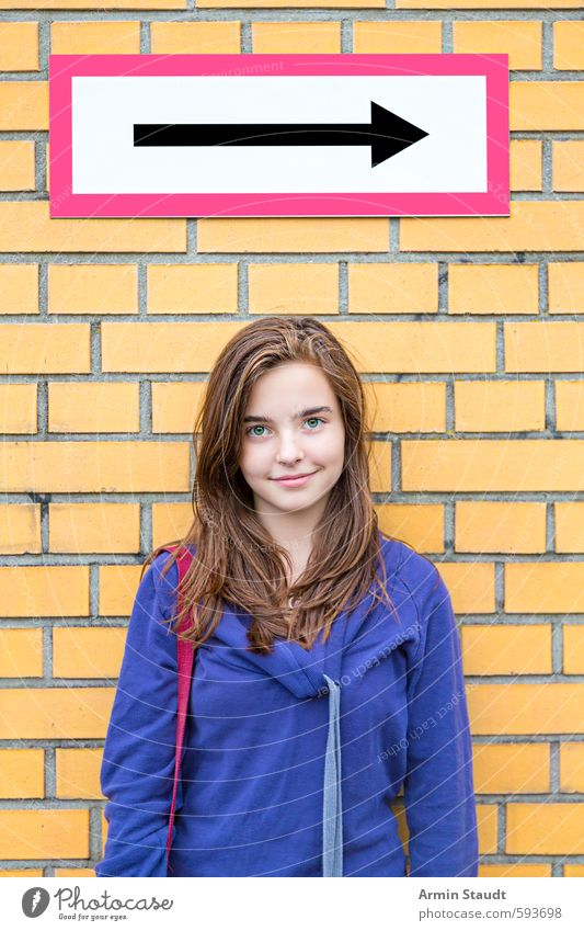 Smiling girl in front of a brick wall/direction arrow Lifestyle Human being Feminine Woman Adults Youth (Young adults) 1 13 - 18 years Child Wall (barrier)