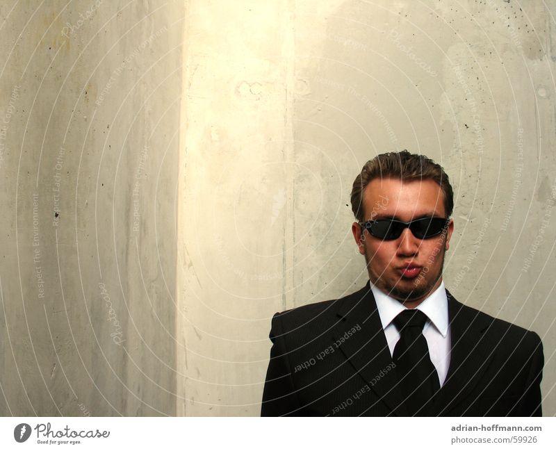 """Küsch misch"" Man Fellow Gentleman Fine Suit Black Sunglasses Kissing Lips Pointed Grimace Facial hair Concrete Gray Wall (building) Ridiculous Strange Stupid"