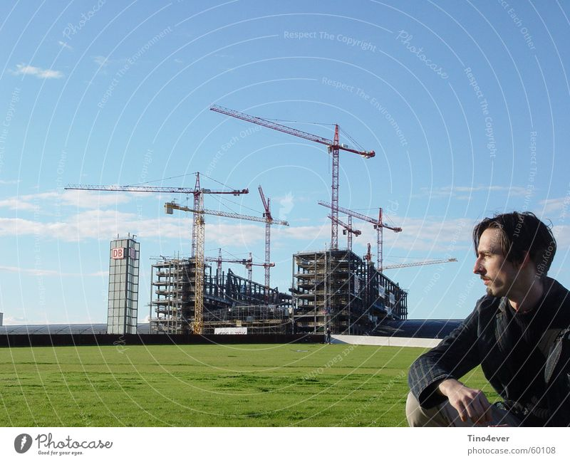 Man in front of Lehrter Central Station Side Grass Meadow Clouds Construction crane Crane Light blue Railroad Train station more teacher Berlin Sky
