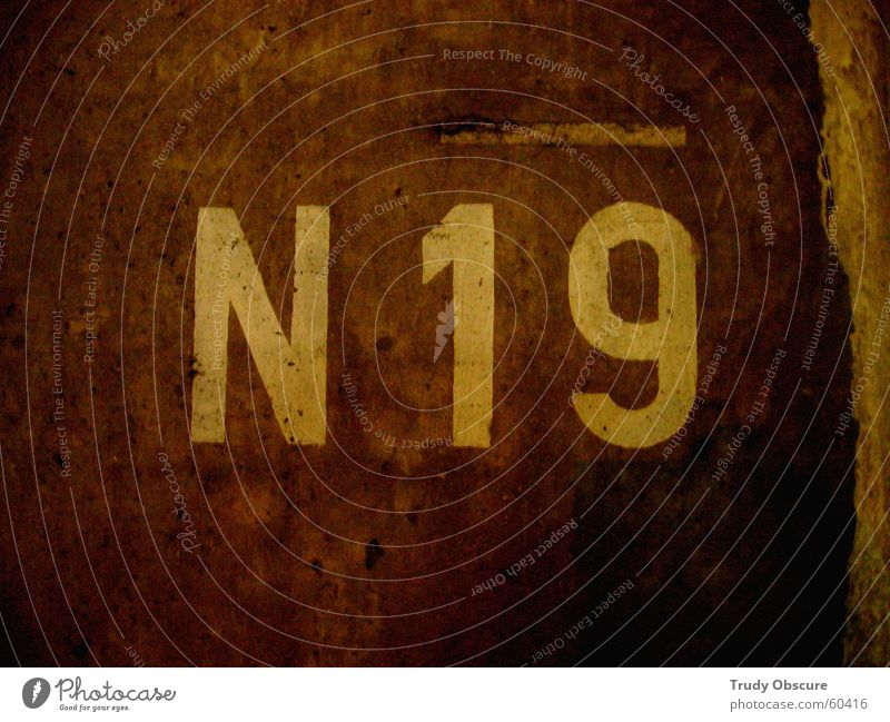 N - nineteen - 19 Background picture Wall (building) Wall (barrier) Surface Concrete Digits and numbers Letters (alphabet) Characters Brown Dark Illogical
