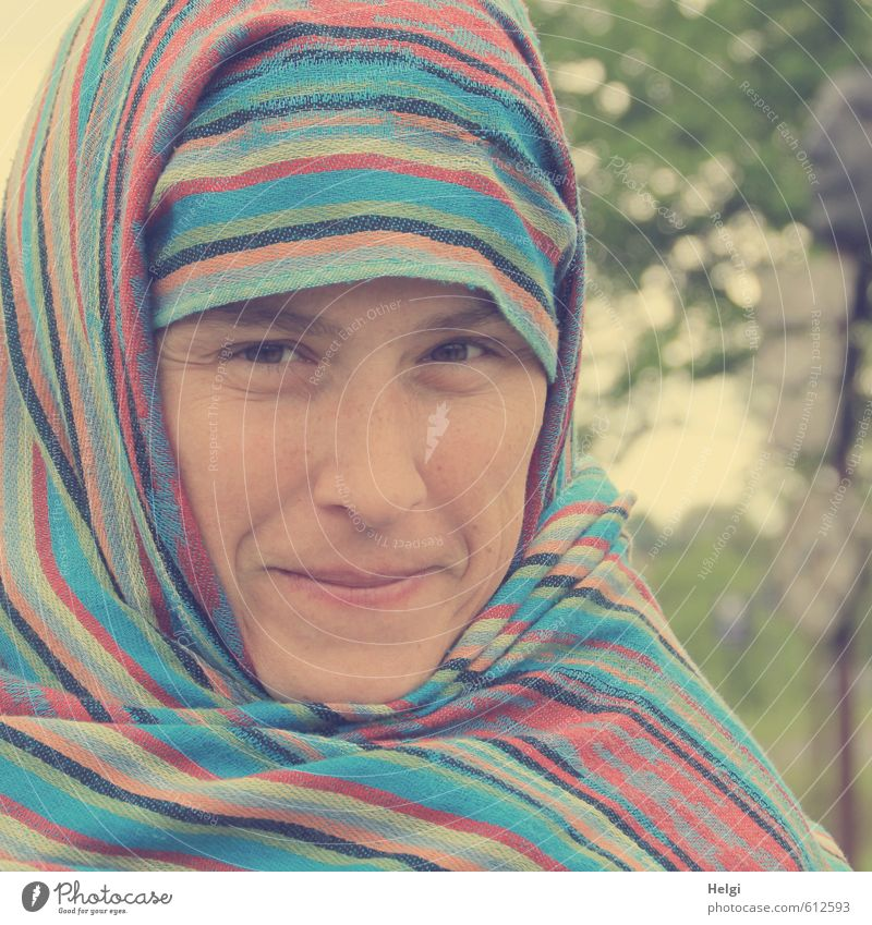 Portrait of a smiling woman who has wrapped her head in a colourful striped scarf Human being Feminine Woman Adults Face 1 30 - 45 years Headscarf Smiling