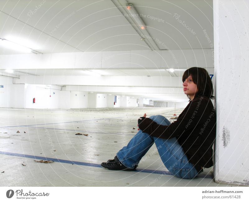Alone in the underground car park Woman Sit Underground garage Wall (building) Neon light Fluorescent Lights Parking garage Leaf Sterile Future Far-off places