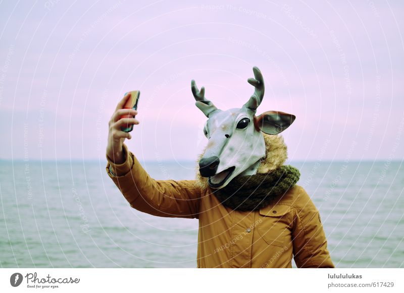 It's a reindeer. Carnival Human being Feminine Face 1 Nature Sky Beach Ocean Jacket Mask Animal Reindeer Smiling Stand Happiness Large Hip & trendy Joy