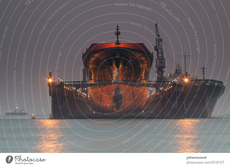 On the dry Construction site Economy Logistics Water Sunrise Sunset Fog Ocean Navigation Container ship Dry dock Threat Dark Gigantic Blue Violet Far-off places