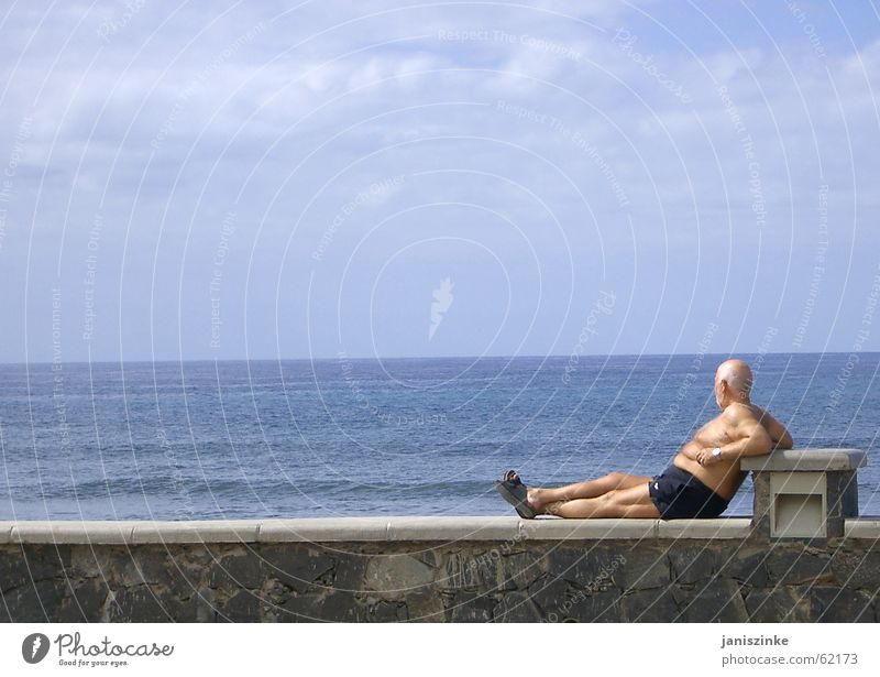 quiet seat Man Wall (barrier) Stone Ocean Swimming trunks Sandal Shuffle Vacation & Travel Bald or shaved head Beer belly Vantage point Tourist Lake Horizon