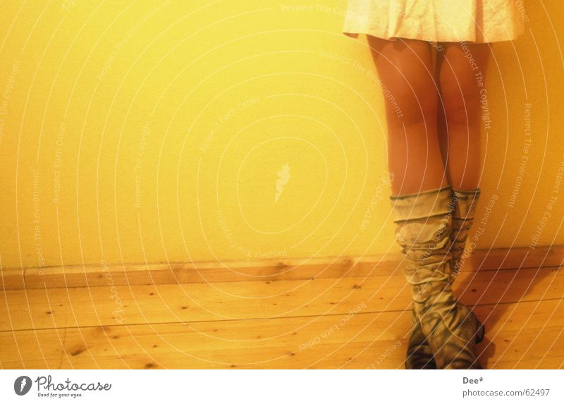 dirty Woman Yellow Stand Boots Wall (building) Wooden floor Thigh Calf Legs Human being Wait Skin Lean Shadow