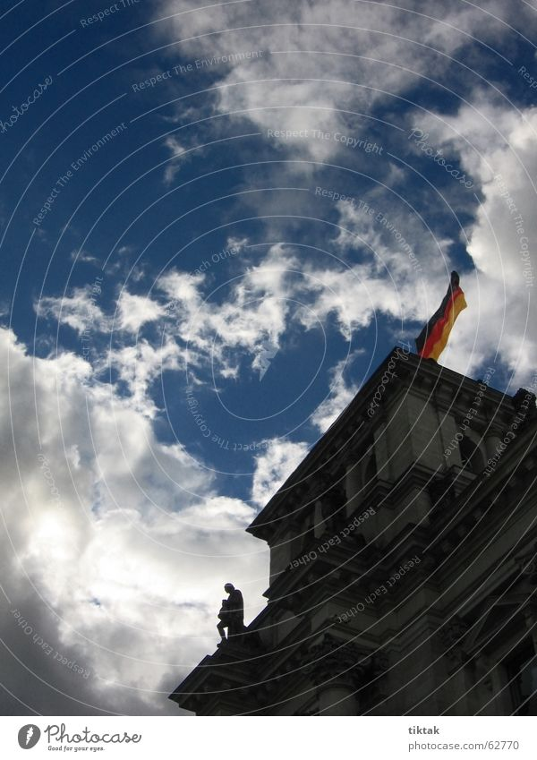 Reichstag in the dark Clouds Gray Dark Flag Historic Politics and state Government Statue Gale Dramatic Back-light Above Berlin Blue Blow federal flag Germany