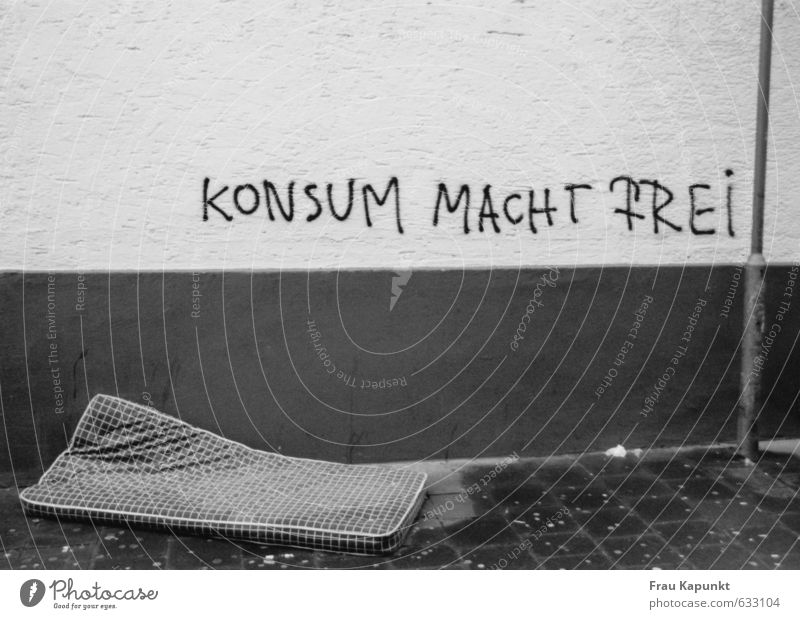 Consumption makes you free. Wall (barrier) Wall (building) Lamp post Sidewalk Mattress Graffiti Wet Fear of the future Inequity Deserted Poverty Freedom Society