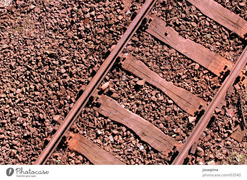 three materials Railroad tracks Transport Wooden board Gravel Sunlight Evening sun Light Deep Wanderlust Right ahead Passenger train Freight train