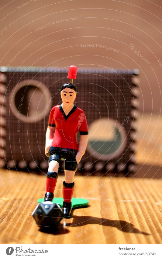 The ball has corners 2.... Red Black Green Brown Wood White Shadow Statue Sports goal wall Table soccer Wood grain 1 Shallow depth of field Colour photo Goal
