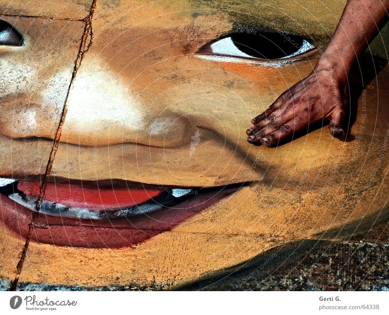 Street painting, portrait of a baby face on stone slabs with the artist's hand in the picture Hand Asphalt Evil Red Black Painting and drawing (object) Art