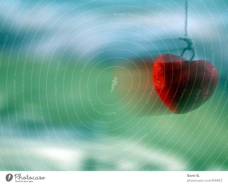 red heart with motion blur at the right edge of the picture in front of a green-blue background Red Green Speed Motion blur Swing String Love Peace Heart Blue