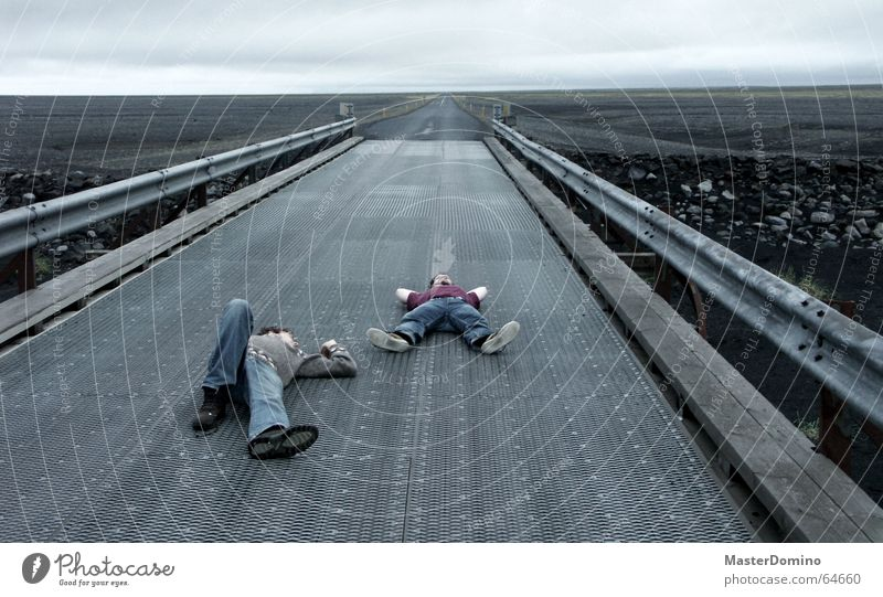 midnight nap Man Human being Sleep Relaxation Horizon Lava Gray Iceland Extreme Dark Cozy Comfortless Crash barrier Clouds Sky Bad weather Freedom Exterior shot