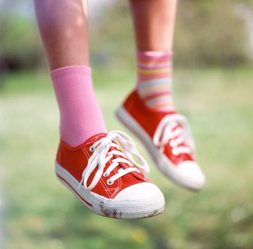 I sit here on my tree... Sneakers Footwear Red Stockings Striped socks Difference Shoelace Pink Calf Meadow Grass Exterior shot Depth of field Child Girl