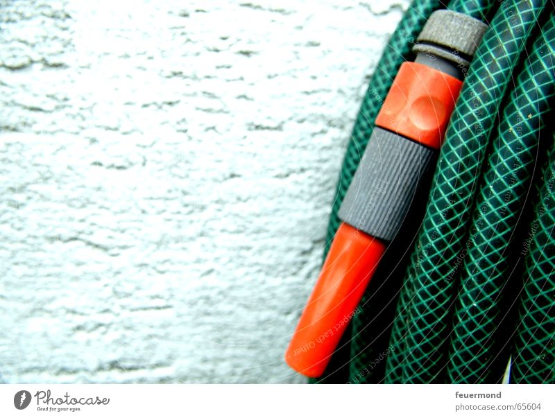 Garden hose instead of watering can Hose Wall (building) Plaster Cast Refrigeration Green Water hose Rain nozzle Inject Orange hosepipe