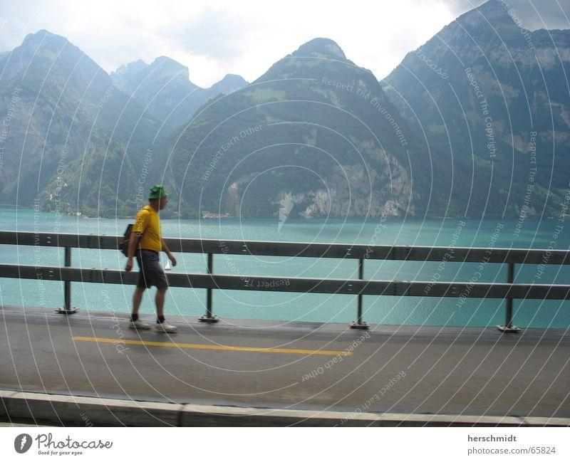 mountain tour Lake Man Yellow Going Backpack Sidewalk Cap Mountain Water Street Sky